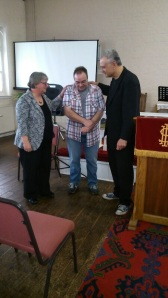 Jackie Clarke (left) and Stewart Bloor (right) praying with Steve Hadley as he becomes an elder at TFC.